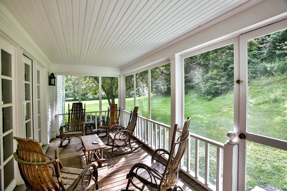 This is the screened porch of the guest house with multiple wooden rocking chairs around a wooden coffee table. Image courtesy of Toptenrealestatedeals.com.