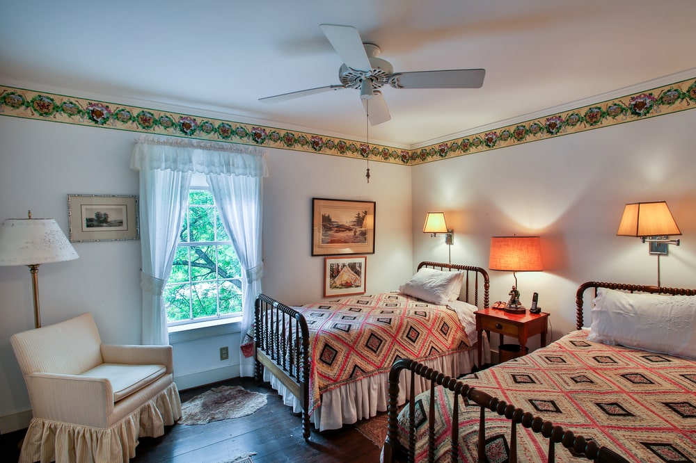This other bedroom of the main house has a couple of wrought-iron bed flanking a wooden bedside table topped by a table lamp. Image courtesy of Toptenrealestatedeals.com.