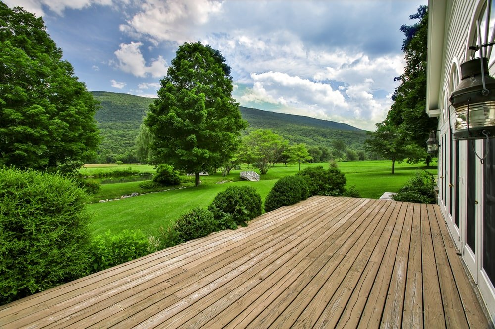 This is the wooden deck just outside the glass French doors of the main house's living room adorned with a lush green landscape. Image courtesy of Toptenrealestatedeals.com.