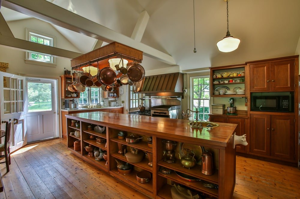 The kitchen of the main house has a large wooden kitchen island topped with a pot rack from the beige cathedral ceiling with exposed beams. Image courtesy of Toptenrealestatedeals.com.