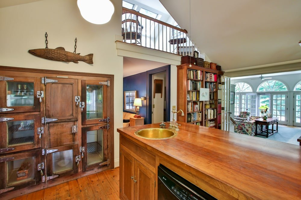 This other view of the kitchen shows the vintage ice box on the wall by the kitchen island with a bowl sink. Image courtesy of Toptenrealestatedeals.com.
