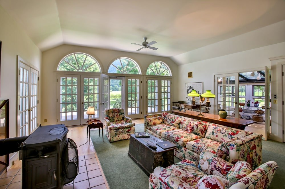 This is the living room of the main house with a floral sofa set, a wooden coffee table and a row of arched French glass doors. Image courtesy of Toptenrealestatedeals.com.