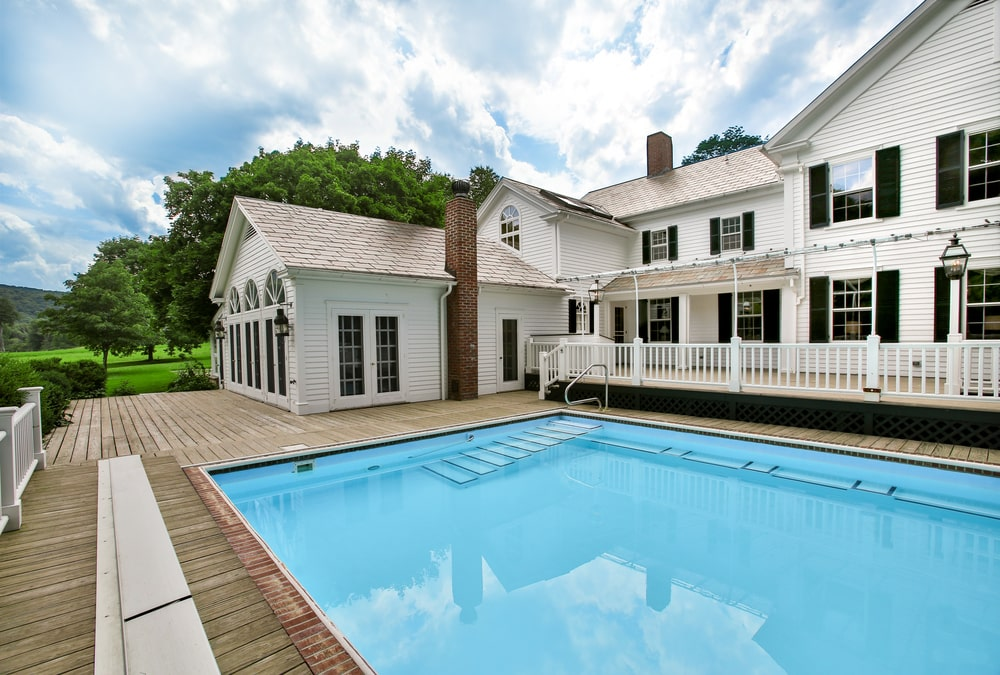 This is a look at the back of the main house showcasing the large swimming pool. You can see here the bright white exteriors of the house accented with windows and chimneys. Image courtesy of Toptenrealestatedeals.com.