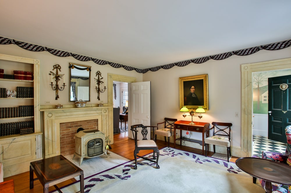 This is the parlor of the main house with a beige fireplace mantle that blends with the walls that are adorned with wall-mounted artworks. Image courtesy of Toptenrealestatedeals.com.