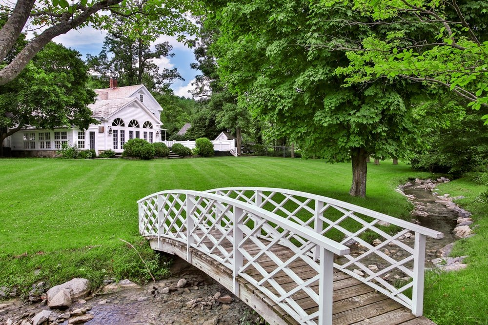 a few yards from the main house is a stream that can be crosed with this small white wooden bridge that stands out against the green lawn. Image courtesy of Toptenrealestatedeals.com.
