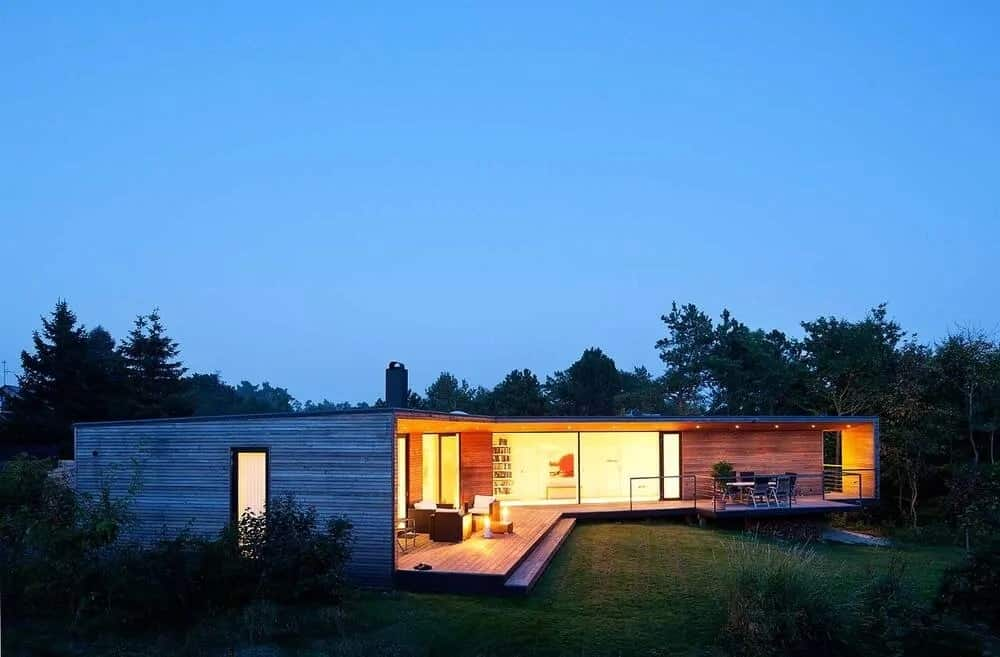 This is a warm minimalist house with a large wooden deck porch that lines the sides of the house complemented by the large open walls that glow from the interior lights.