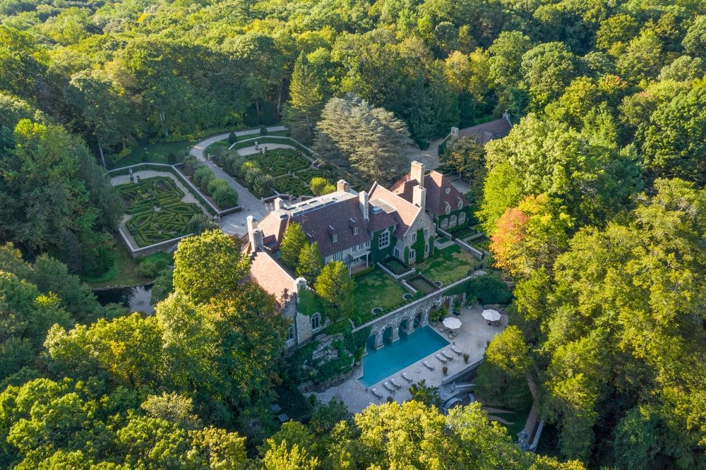 This other aerial view of the mansion showcases the outdoor areas at the back like the pool and gardens. These are all surrounded by a thick landscape of tall trees. Image courtesy of Toptenrealestatedeals.com.