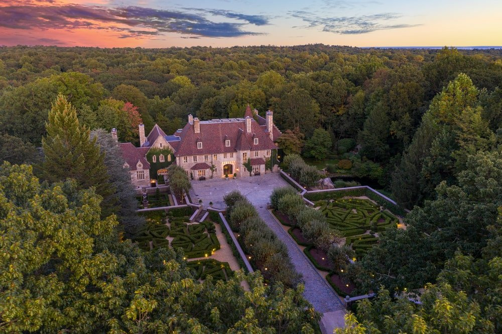 This is an aerial view of the mansion shwcasing the large driveway flanked by tall trees leading to a large courtyard in front of the house. Image courtesy of Toptenrealestatedeals.com.