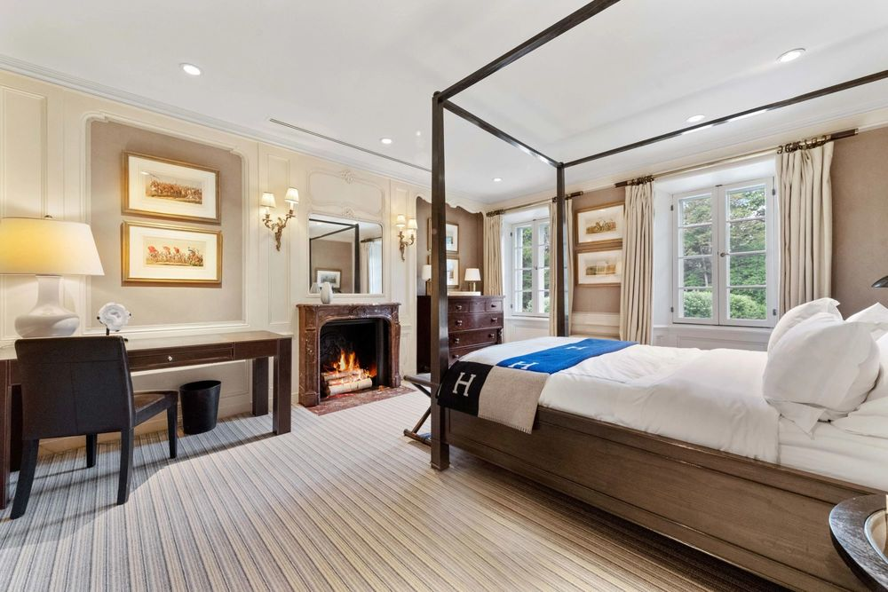 This bedroom has a dark-toned four-poster bed across from the fireplace with a wooden mantle. Image courtesy of Toptenrealestatedeals.com.