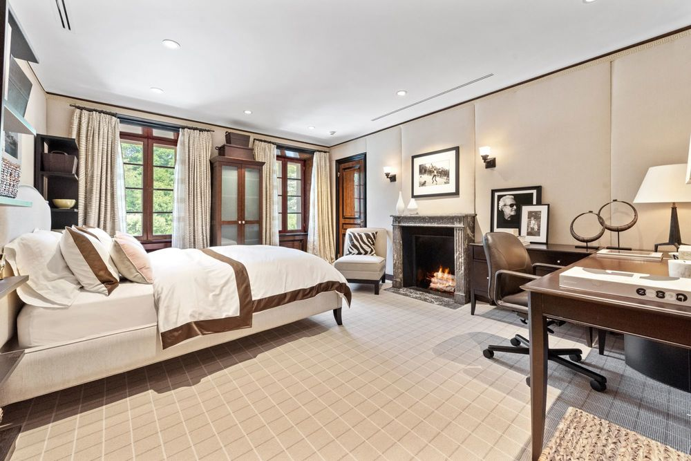 This bedroom has a beige bed across from the fireplace that is topped with a painting and wall sconces on a beige wall. Image courtesy of Toptenrealestatedeals.com.