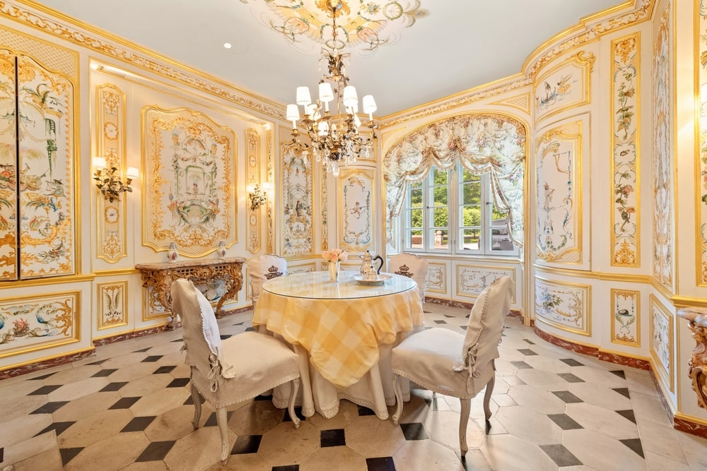 This formal dining room has a light beige tone to its paneled walls that matches with the chandelier and the table cloth of the round dining table. Image courtesy of Toptenrealestatedeals.com.