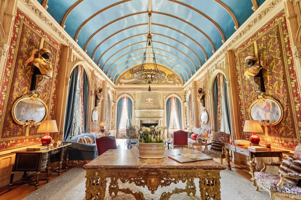 This family room has a tall cove ceiling with a mural of the sky. This is complemented by the paneled walls with rows of tall arched windows. Image courtesy of Toptenrealestatedeals.com.