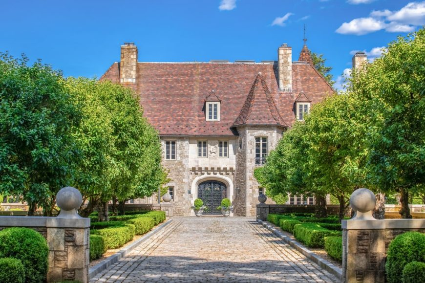 This is a front view of the mansion with an Old World craftsmanship, dormer windows, stone exteriors and tall chimneys. These are adorned by a wide driveway flaked by mature apple trees. Image courtesy of Toptenrealestatedeals.com.