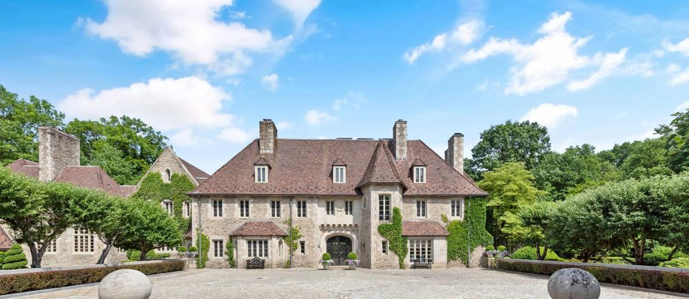 This is a front view of the large stone mansion showcasing the dormer windows, tall chimneys and a large courtyard in front. Image courtesy of Toptenrealestatedeals.com.