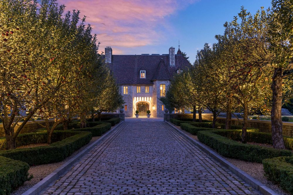 This is a nighttime view of the front of the house showcasing the warm glow of the main entrance. This is paired with the outdoor lighting that makes the flanking trees glow. Image courtesy of Toptenrealestatedeals.com.