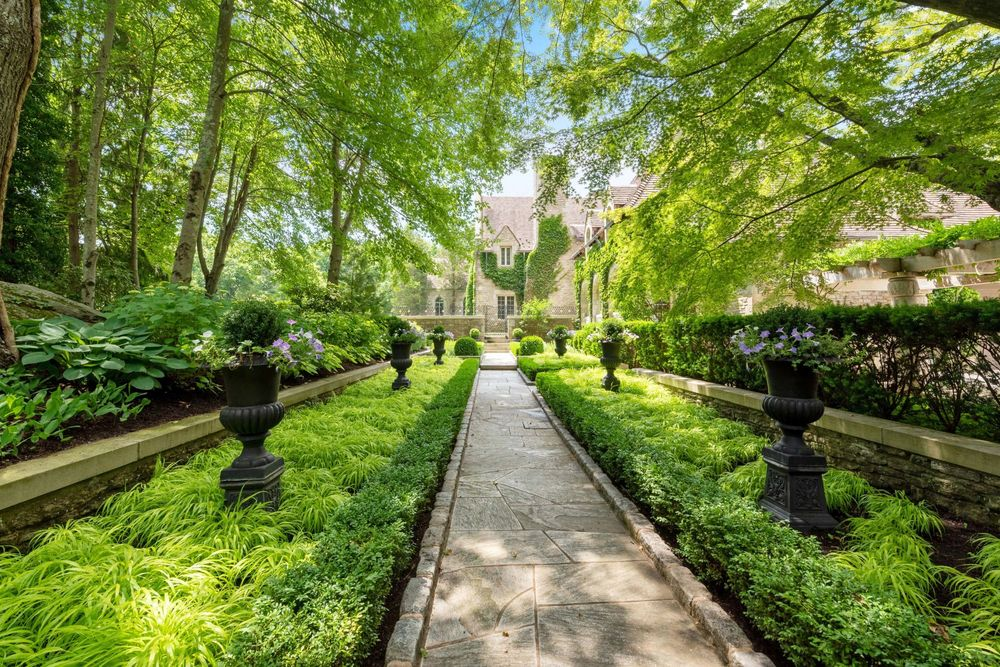 This look at the garden showcases the planters placed in intervals among the shrubs flanking the walkway topped with a canopy of tall trees. Image courtesy of Toptenrealestatedeals.com.