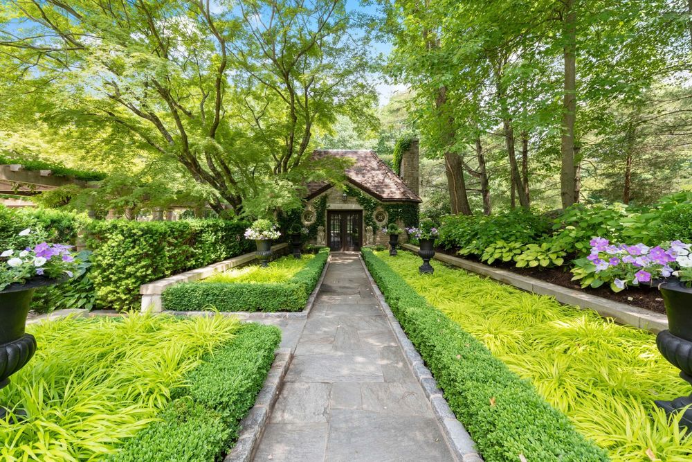 This concrete walkway leads to a side entrance of the house where the exterior walls are adorned with creeping plants and tall trees. Image courtesy of Toptenrealestatedeals.com.