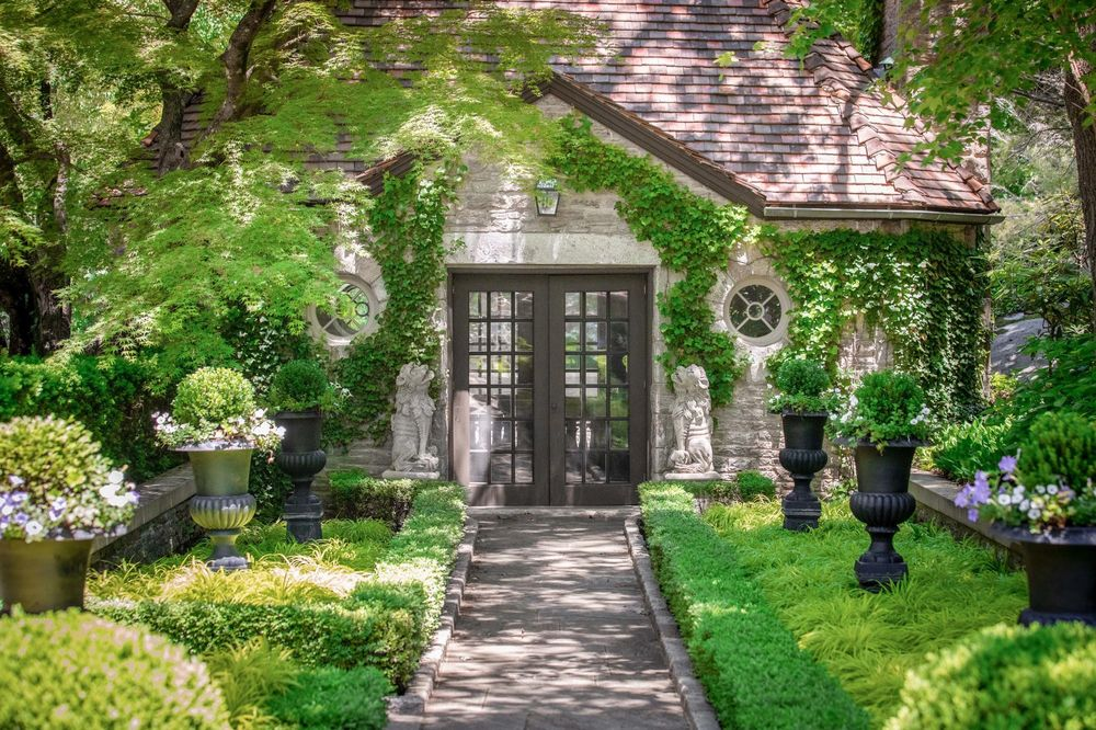 This is a closer look at the side entrance of the house with a set of French glass doors leading to the walkway flanked with shrubs and planters. Image courtesy of Toptenrealestatedeals.com.