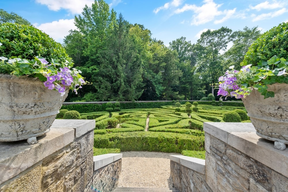 This is a look at the backyard garden from the vantage of the stone steps flanked with potted plants and low stone walls. Image courtesy of Toptenrealestatedeals.com.