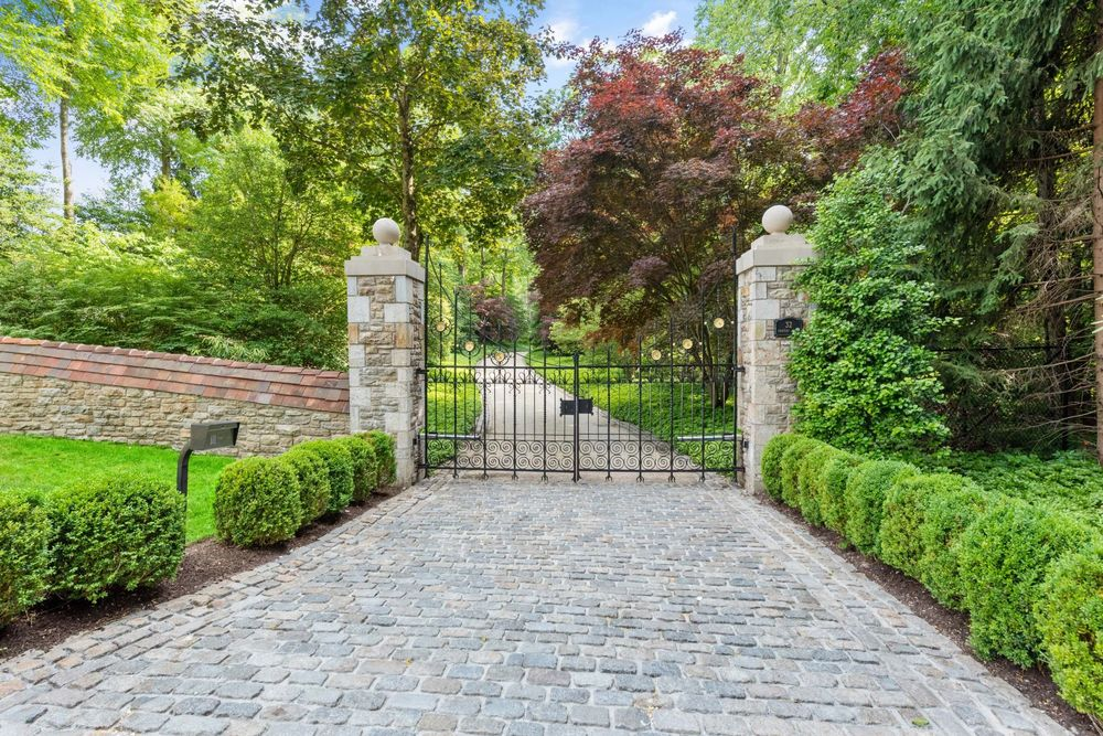 This is a look at the main gate of the property from the vanatge of the driveway. This has a wrought-iron gate supported by a couple of stone pillars with outdoor lamps. Image courtesy of Toptenrealestatedeals.com.