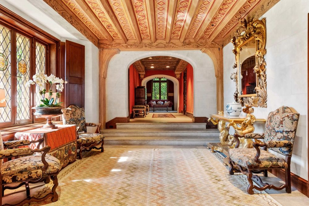 This is a look at one of the hallways of the mansion fitted with comfortable cushioned armchairs and adorned with console tables and a large golden mirror. Image courtesy of Toptenrealestatedeals.com.