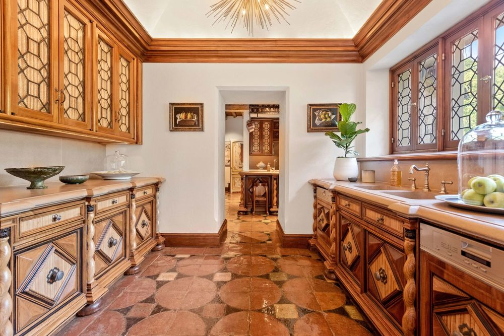 This other view of the kitchen shows the brown tone of the flooring tiles that match the wooden molding and wooden cabinetry with superb craftsmanship. Image courtesy of Toptenrealestatedeals.com.