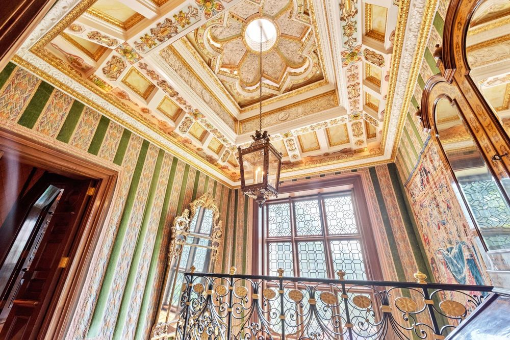 This is a look at the tall ceiling of the second-floor landing. It has a patterned and carved tray ceiling that hangs a large lantern pendant light over the staircase. Image courtesy of Toptenrealestatedeals.com.