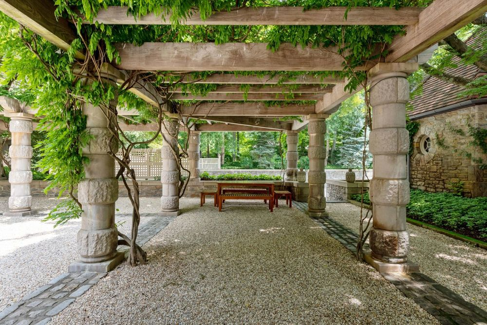 This part of the outdoor area shows a covered area with stone pillars supporting trellises with creeping plants to provide shade for the wooden bench at the far end. Image courtesy of Toptenrealestatedeals.com.