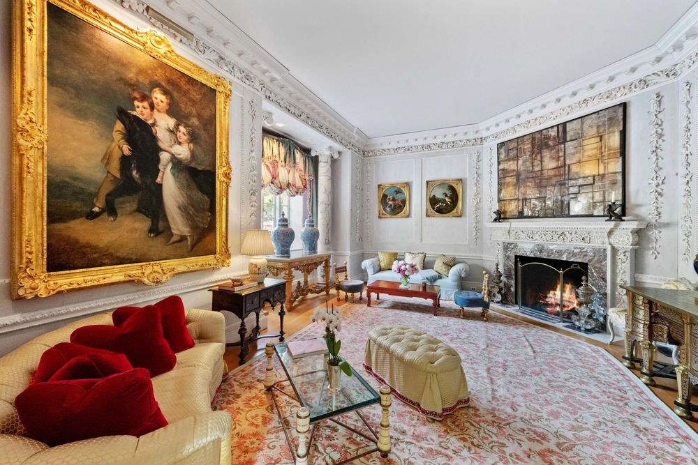 This spacious living room has a large fireplace that warms the sofas adorned with wall-mounted artworks. Image courtesy of Toptenrealestatedeals.com.