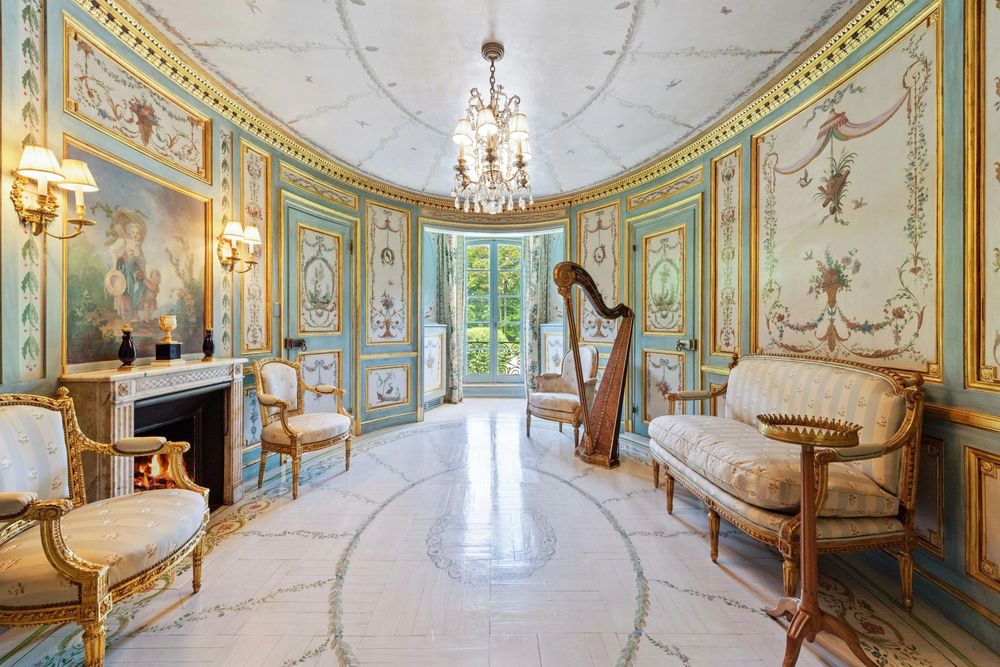 This is the music room with paneled walls, a chandelier in the middle, and a fireplace across from the sofa. Image courtesy of Toptenrealestatedeals.com.