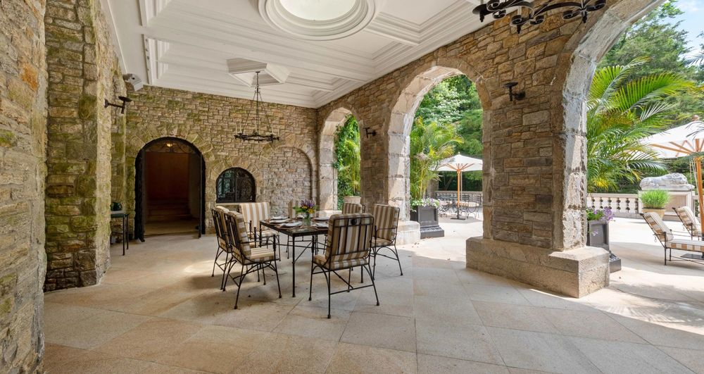 This is the covered patio fitted with an outdoor dining set that has a background of arches, and stone pillars. Image courtesy of Toptenrealestatedeals.com.