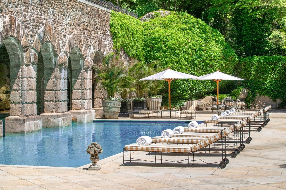 This is the pool area with multiple lawn chairs and large umbrellas with a background of trees and shrubs. Image courtesy of Toptenrealestatedeals.com.