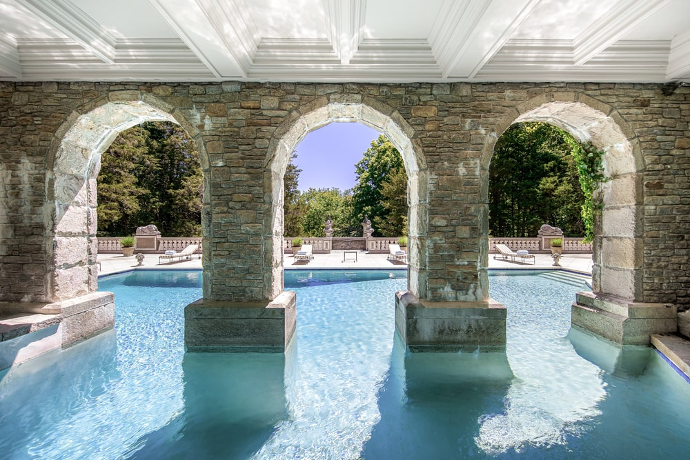 This is the covered part of the pool with a white coffered ceiling, arches and pillars of stone. Image courtesy of Toptenrealestatedeals.com.
