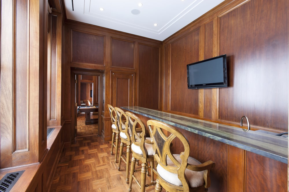 This is the bar with a row wooden stools. The bar has a dark wooden tone that blends well with the wall behind it with a wall-mounted TV. Image courtesy of Toptenrealestatedeals.com.