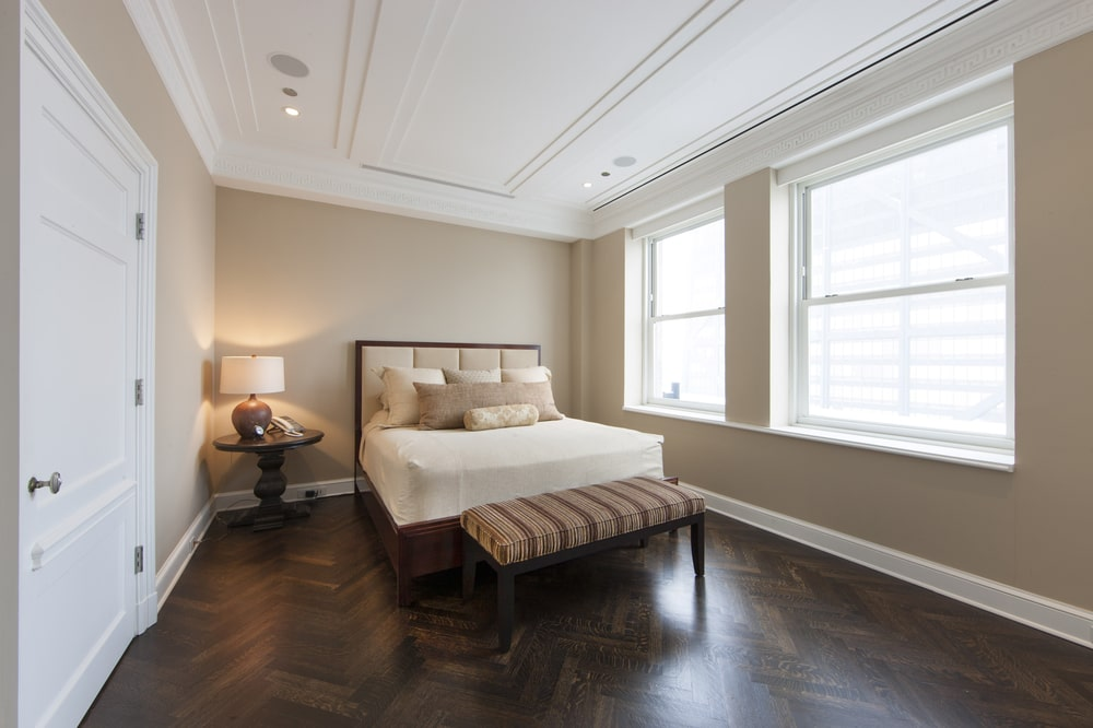This bedroom has a dark hardwood flooring with herring bone patterns. This pairs well with the wooden frame of the bed that is contrasted by the white sheets. Image courtesy of Toptenrealestatedeals.com.