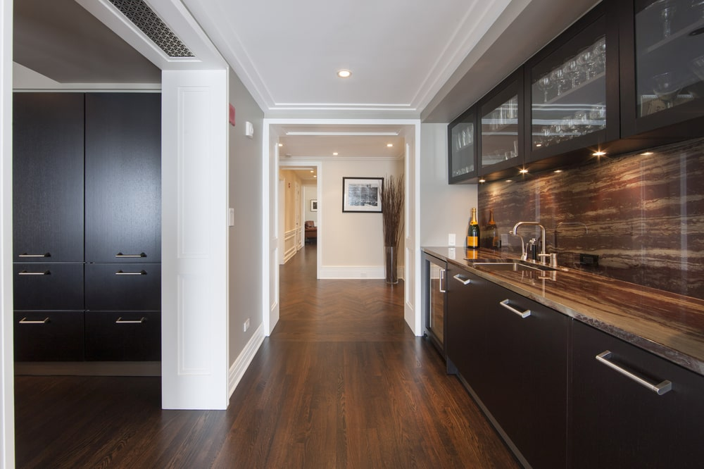 The kitchen has dark wooden cabinetry lining the walls that contrast with its light beige tones. These are all complemented by the bright white ceiling with recessed lights. Image courtesy of Toptenrealestatedeals.com.