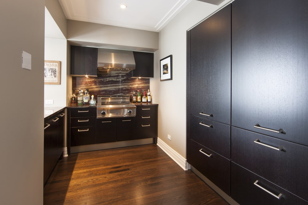 The other side of the kitchen has more dark wooden cabinetry that blends well with the floor. These make the modern silver handles stand out. Image courtesy of Toptenrealestatedeals.com.