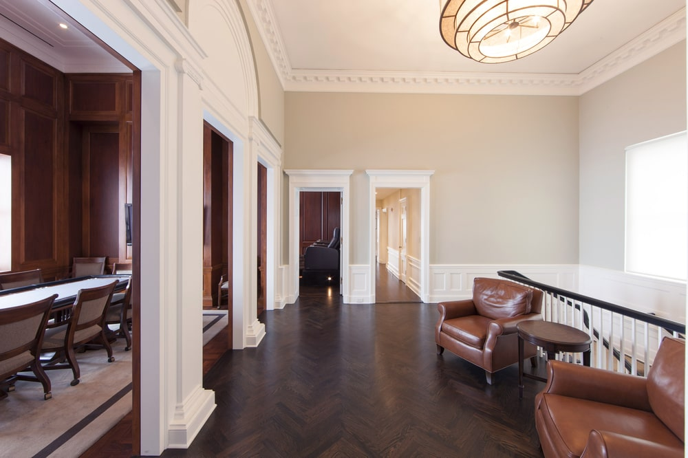This is the spacious second-floor landing with dark hardwood flooring that contrasts the bright beige walls and ceiling with a pendant light over the couple of cushioned armchairs. Image courtesy of Toptenrealestatedeals.com.