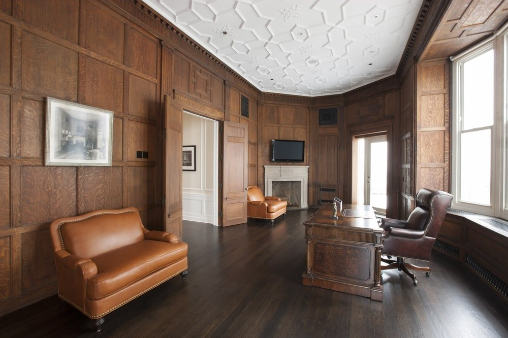 This is the spacious home office with dark wooden walls to match the floor and the desk paired with a leather chair. Image courtesy of Toptenrealestatedeals.com.