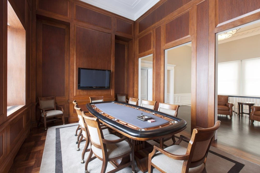 Next to the pool table room is the poker room with its own professional poker table surrounded by dark wooden walls with a wall-mounted TV. Image courtesy of Toptenrealestatedeals.com.