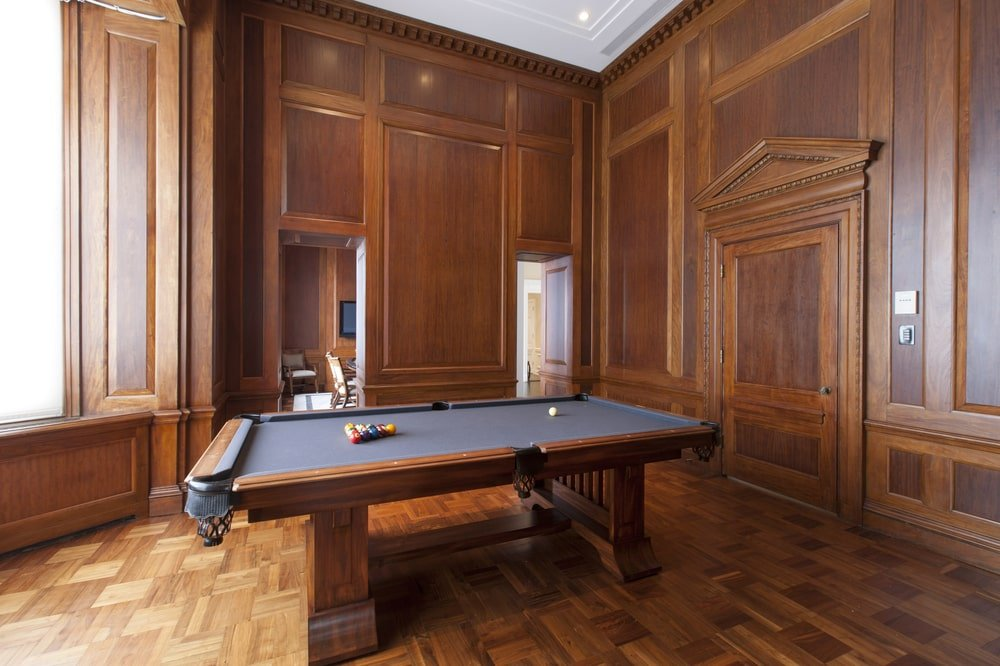 This is a close look at the pool table that is surrounded by consistent dark wooden tones on the walls, floor and doors. This makes the gray top of the table stand out. Image courtesy of Toptenrealestatedeals.com.
