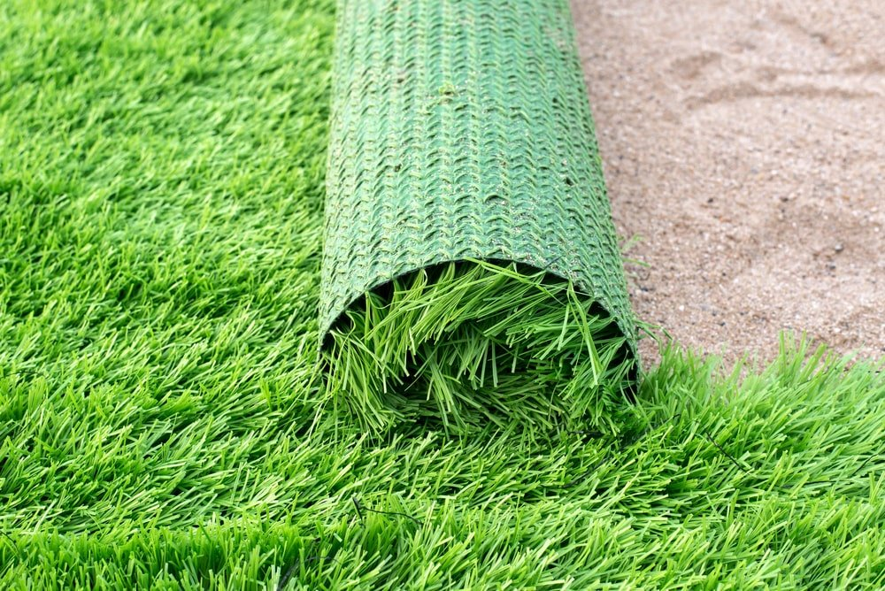 A roll of artificial grass carpet being installed onto a sandy ground.