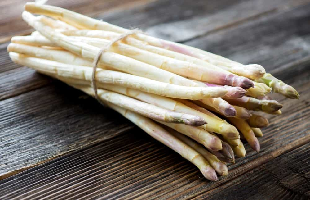 A bundle of white asparagus on a rustic table.
