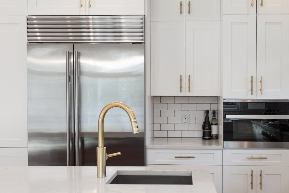 White kitchen with shaker cabinets, subway tile backsplash, white granite countertop, stainless steel appliances, and brushed gold faucet.