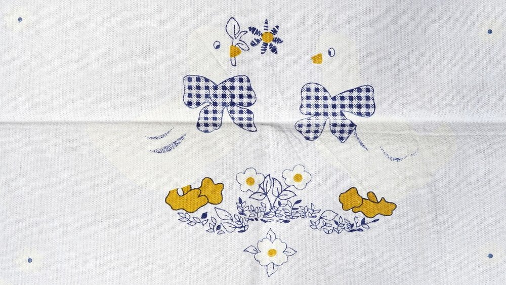 White cloth with prints of chickens, ribbons, and flowers.