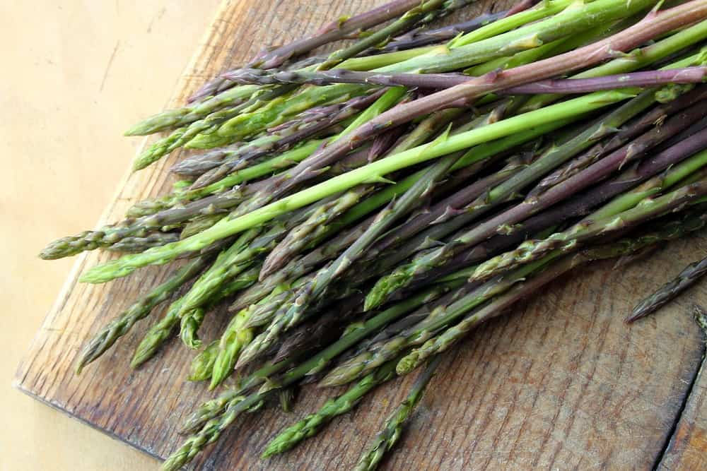 Wild asparagus on a wooden chopping board.