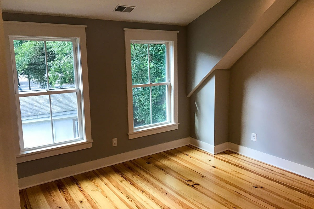 The bedroom has a vaulted ceiling, natural hardwood flooring, and a pair of white-framed windows.