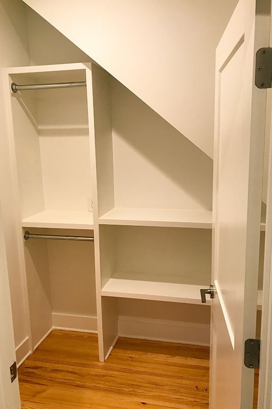 The walk-in closet is filled with built-in shelves that match the white door.