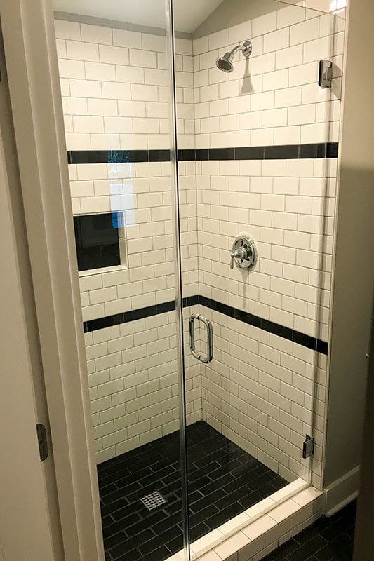Walk-in shower with white subway tile walls, inset shelf, and chrome fixtures.