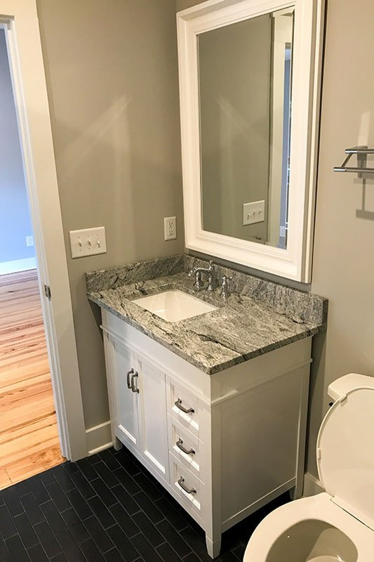 The bathroom is equipped with a toilet and a granite top vanity placed under the rectangular mirror.